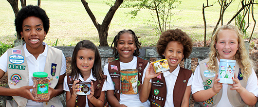 Girl Scouts sitting on a bench and holding up various fall product program items