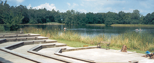 Wooden bench seating around a firepit next to a lake at Camp Robinwood in Willis, Texas.