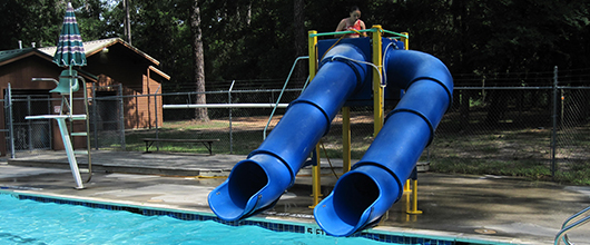 Two water slides next to a pool at Camp Silver Springs in Conroe, Texas.